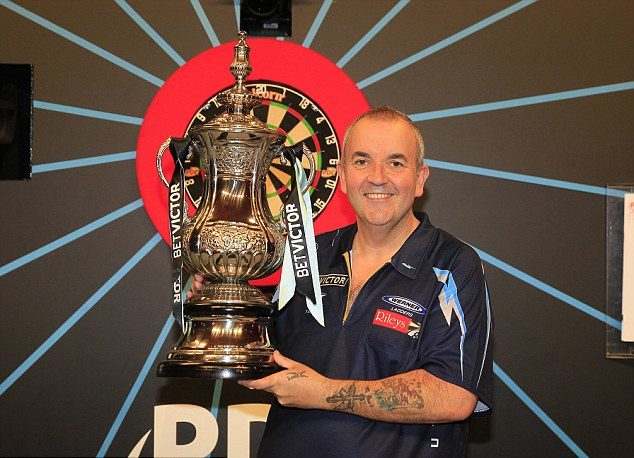 Phil Taylor holding up his 15th world wide matchplay title trophy